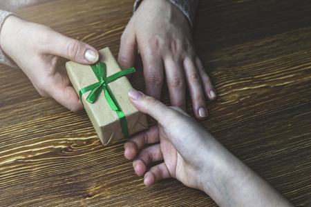 Girl gives a woman a gift box with a green ribbon 版權商用圖片