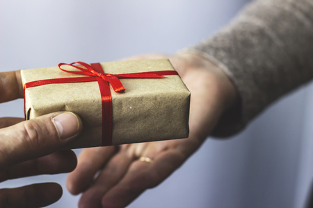A man gives a woman a gift with a red ribbon