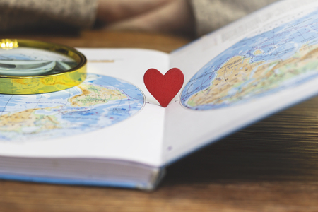 Little red heart stands in a textbook with a map of the world, close-up Stock Photo
