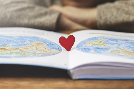Little red heart stands in a textbook with a map of the world Stock Photo