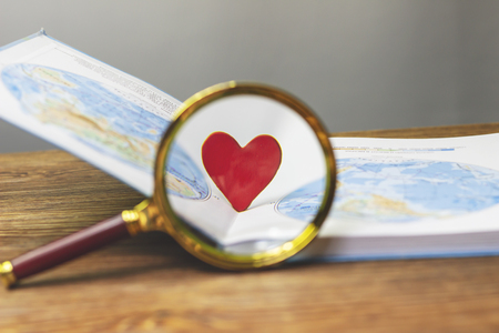 A small red heart magnified by a magnifying glass stands in a textbook with a map of the world Stock Photo