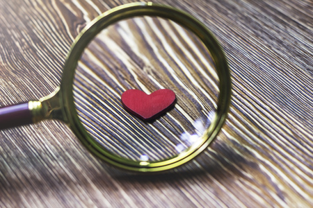 Little red heart magnified by a magnifying glass