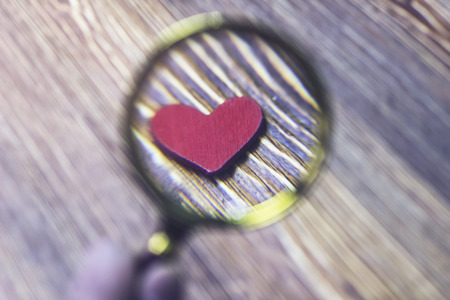 Little red heart magnified by a magnifying glass, close-up