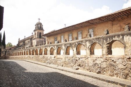 Long street showing a row of arches on the facade leading to the church in a Mexican town