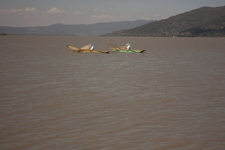 Pair of fishermen paddling to move their canoes loaded with fishing nets sailing through lake in Patzcuaro Michoacán Mexico spontaneous photography with natural light 版權商用圖片