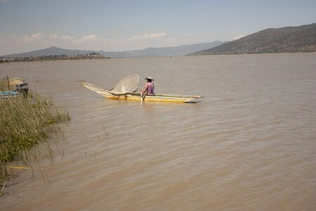 fisherman whit hat paddling to sail with canoes laden with fishing net the lake in Mexico 版權商用圖片