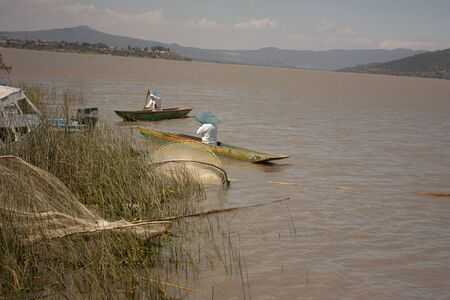 Pair of fishermen paddling to move their canoes sailing through lake in Michoacán Mexico spontaneous photography