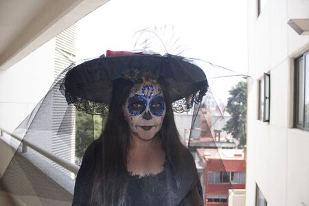 Katrina woman wearing veil and black hat in yellow flower headdress to celebrate the annual Day of the Dead party makeup
