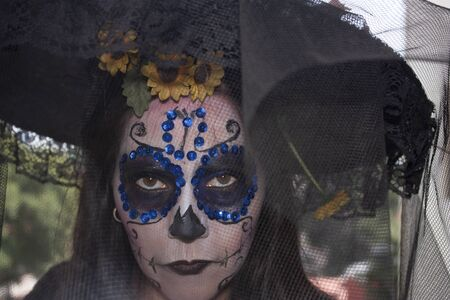 Mexican woman wearing makeup, veil  hat an yellow flowers over  to celebrating the Day of the Dead