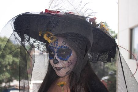 Mexican woman wearing makeup, veil and Katrina hat celebrating the Day of the Dead Traditional makeup and carina hat in Mexico