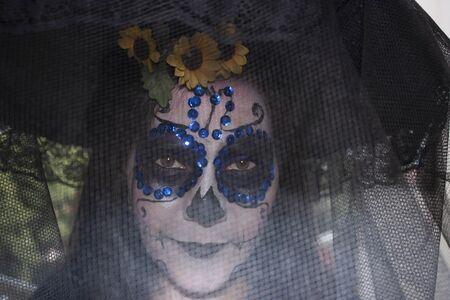 Mexican woman wearing makeup, veil and Catrina hat celebrating the Day of the Dead