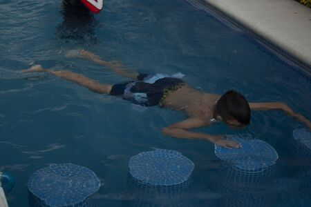 child looking down prone position doing little busts in the water while learning to swim is observed the effect of refraction of light on his body covered with liquid