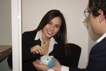 Woman saving part of her salary in the office to generate financial release does so in the presence of the human resources employee