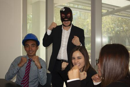 Boss in the office wearing a wrestler mask moves to the team enthusiasm the architect and his companions are motivated and laugh accepting challenges and relaxing, the work team raises their fists demonstrating a winning attitude fearless Фото со стока