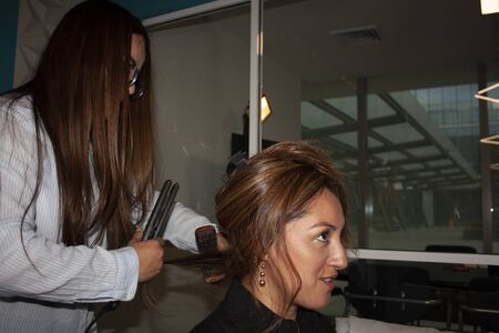 Female straight hair stylist uses pincer beauty tools and brush to comb and stylize the amber hair of a brunette woman in Mexico