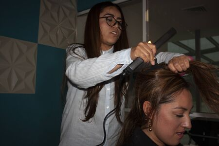 Straight hair stylist woman uses pincer beauty tools and brush using her hands to comb and stylize the amber hair of a brunette woman in Mexico