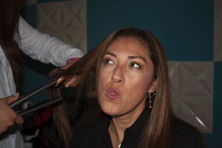 Lips moisturized brown eyes and brown skin of Latin Mexican woman making face gestures while combing her stylize using her hands, tongs and brush