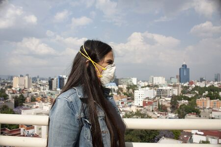 Mexican woman wearing a protector that covers nose and mouth called covers mouths meintas looks towards Mexico City