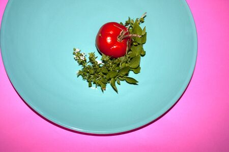 Tomato surrounded by resca branch albhaca with cut flowers from the urban garden Stok Fotoğraf