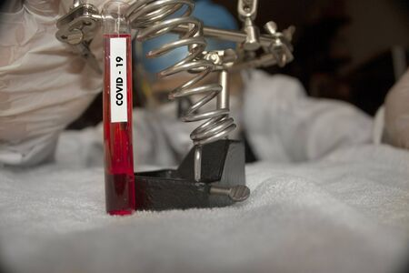 Test tube labeled covid-19 with resting plasma for observation by the biologist pharmaceutical chemist analyzing possible vaccine in Mexico