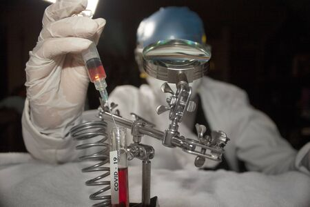 Scientist hand inserting syringe into test tube looking for plasma covid-19 vaccine