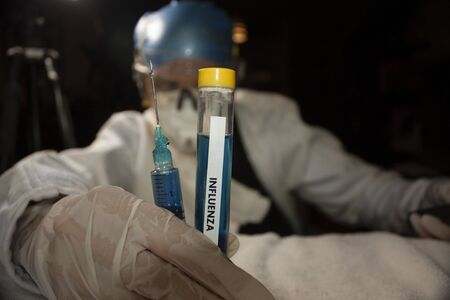 Syringe and container bottle with liquid to biotechnologically analyze new influenza strains for study by a female scientist in Mexico City Reklamní fotografie