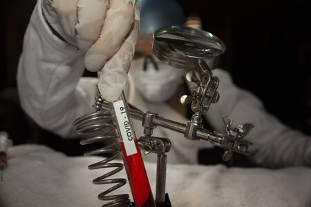 Plasma and blood covid-19 chemical reagents inside test tube for scientific medical studies in Mexico holds the bottle in the hand of a biochemist equipped with protective gloves, lenses and covers mouth