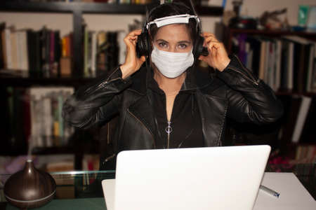 Woman working at home office with a large bookcase behind her using laptop computer on a glass table while the pleasant smelling humidifier in its steam smells the environment