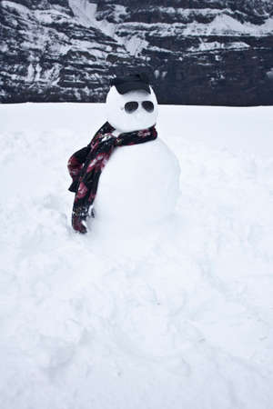 Snowman next to Scarpara de los Ande mountain in Pais de Chile wearing sunglasses and scarf, in Christmas atmosphere among frozen snow