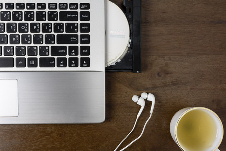 Notebook with cd-r ,earphone and a cup of tea