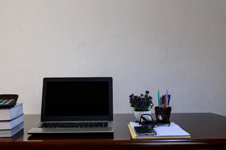 mobilephone: The office desk with laptop,books,calculator,mobile-phone,sheet,pen,glasses and vase of flower. Stock Photo