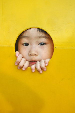 school playground: A little girl sticks her face through a hole in a yellow plastic piece of playground equipment Stock Photo