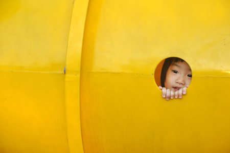 Cute asain girl child peeks through hole of a yellow plastic piece of playground equipment