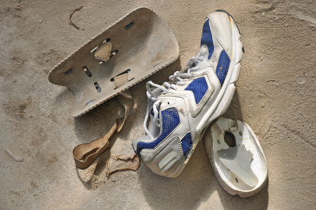 protectors: damaged sport shoe and old used knee protectors of hard sportman