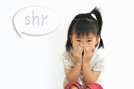 asian small childcovering her mouth with her hands with shy word in speak bubble on white background