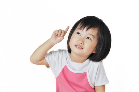 asian small girl child pointing at something above her against a white background