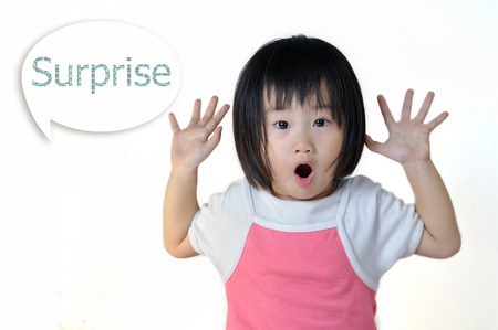 Surprised asian little child open her mounth and raising her hand with surprise word in speak bubble on white background Stock Photo