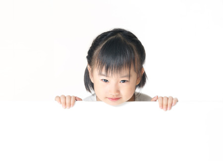 Asian little girl hiding behind a blank white board and peeks over the top