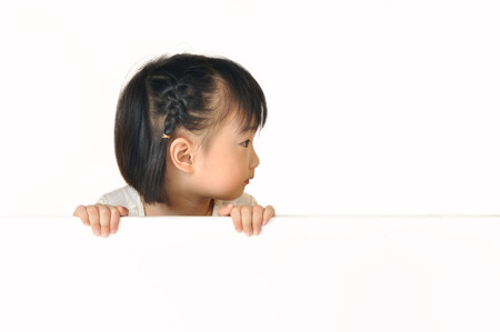 Asian little girl hiding behind a blank white board and see somthing on the right