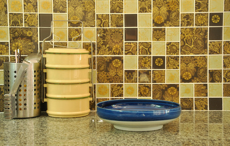 tiffin: Food containers and utencils on asian kitchen counter top; tiffin and porcelain bowl Stock Photo