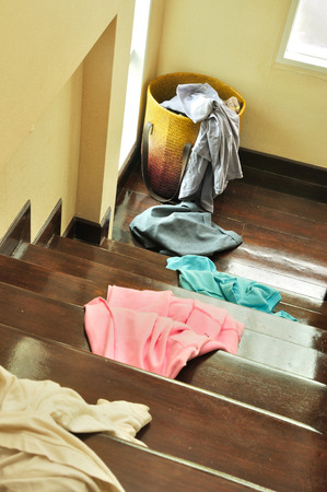 Lots of messy clothes on a cloth basket and stair wooden floor.