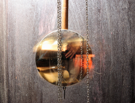 ancient pass: metal pendulum clock swinging in wood background as time pass concept