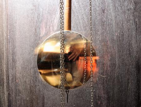 reloj de pendulo: reloj de p�ndulo de metal que hace pivotar en el fondo de madera como concepto que pase el tiempo