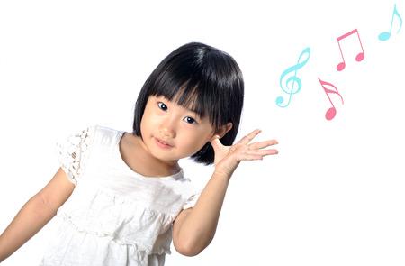 自然の中で音楽を聴く耳を触ると小さなアジアの女の子 写真素材