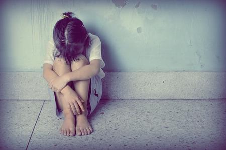 dívka: smutný a depresivní holčička sedí poblíž zdi
