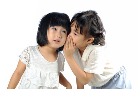 5 years old asian girl whispering to heryounger sister isolated in white background