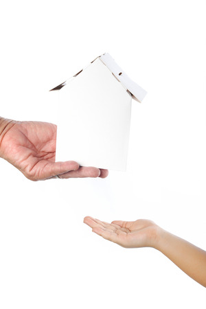 the inheritance: Old womans hand giving paper home to child; concept of inheritance