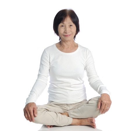 deliberation: senior asian woman doing meditation in buddhism practice against white background Stock Photo