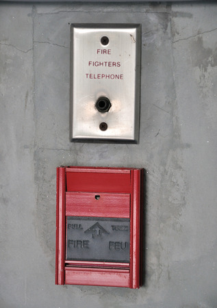 fire fighter: Fire alarm and fire fighter telephone on the concrete wall