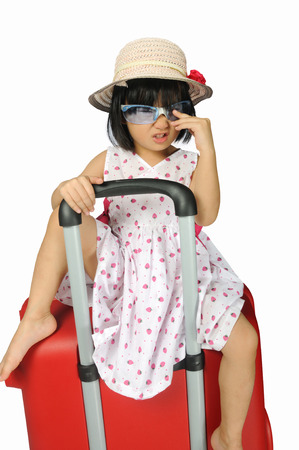 Little asian girl in a weave hat and sunglasses sitting on a huge travel red suitcase in white background photo
